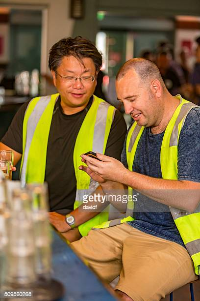 Workmen Looking at Pictures on Phone While Relaxing After Work
