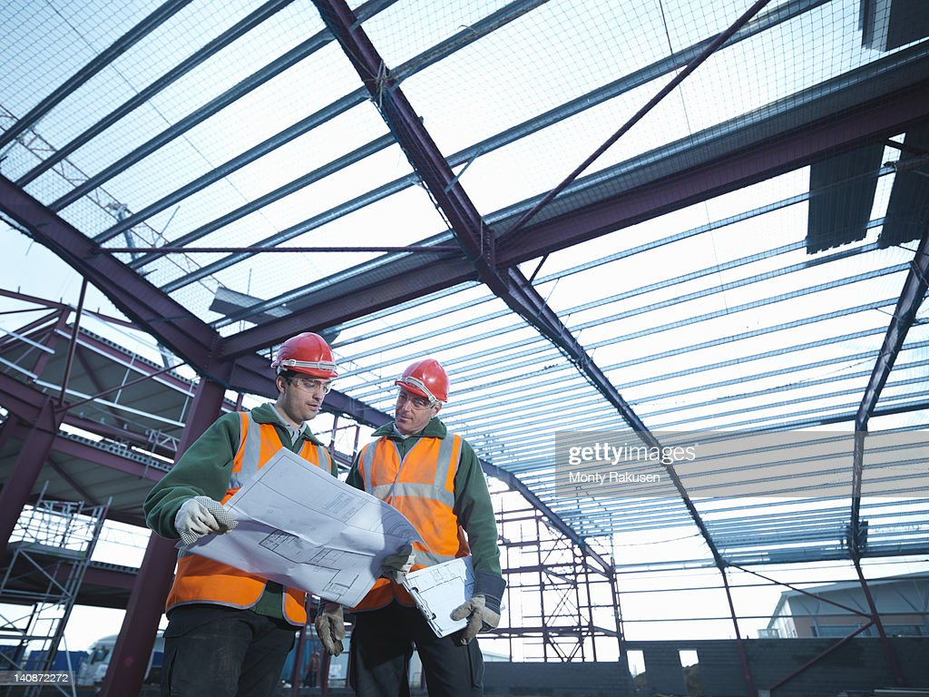 Workmen looking at plans beneath steel construction frame on building site : Bildbanksbilder