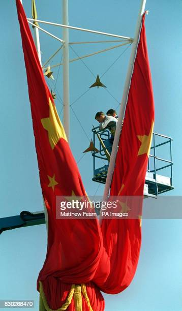 Workmen make adjustments to Chinese flags outside Buckingham Palace in London before the start of the five day State Visit to Britain by President...