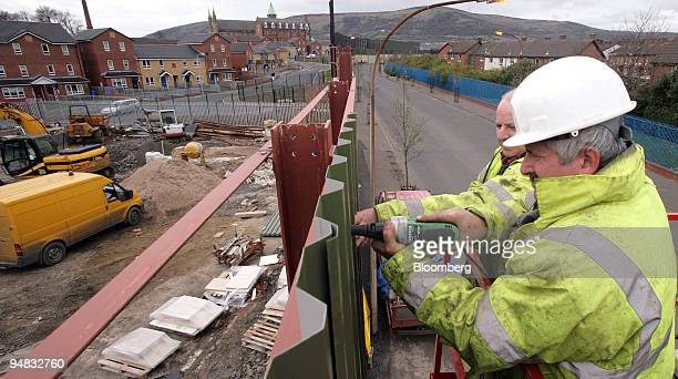 Workmen make repairs to the 'peace line' a 25foot high brick steel and wire structure separating the city's hardline nationalist and unionist...