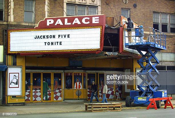 Workmen paint the crumbling marquee above the entrance to the abandoned Palace Theatre on Broadway Street in the old downtown section of Gary Indiana...