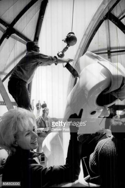 Workmen place 1400Pound declination Axle on telescope mount as Dr Janet Roundtree lesh happily looks on Credit Denver Post