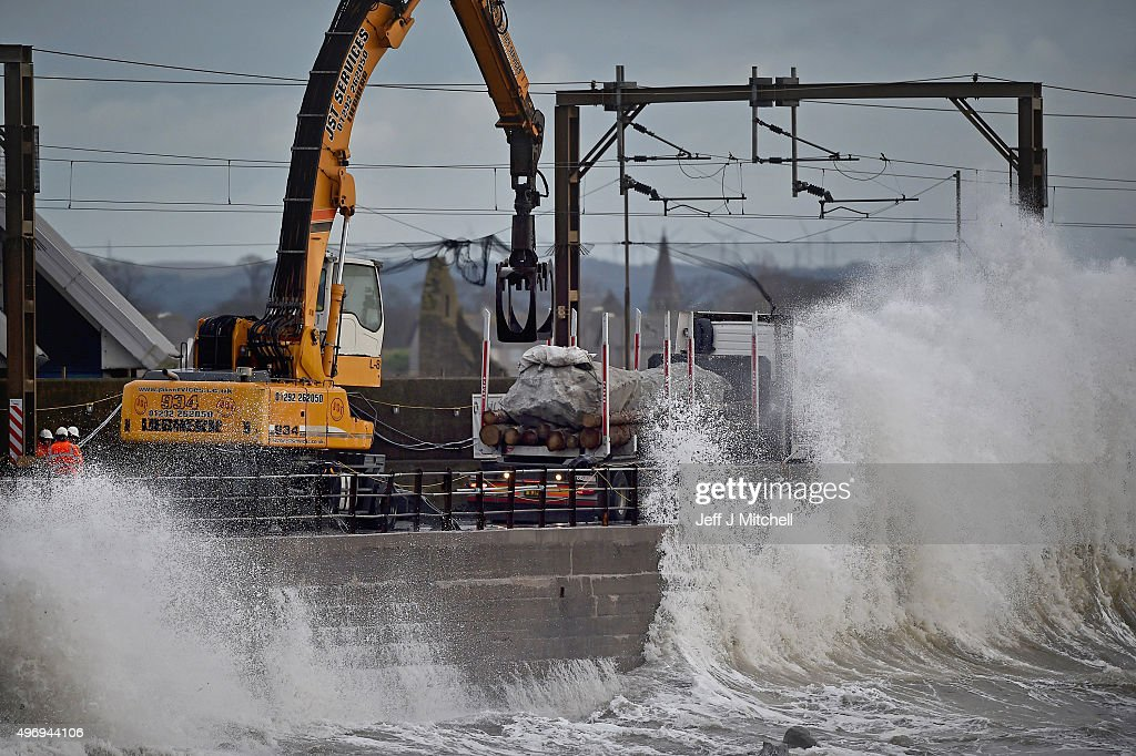 Workmen place large rocks in the sea to bolster flood defences along the sea wall on November 13, 2015 in Saltcoats, Scotland. Storm Abigail has closed schools on the Western Isles and ferries have been cancelled as gale force winds overnight left 12,000 properties without power.