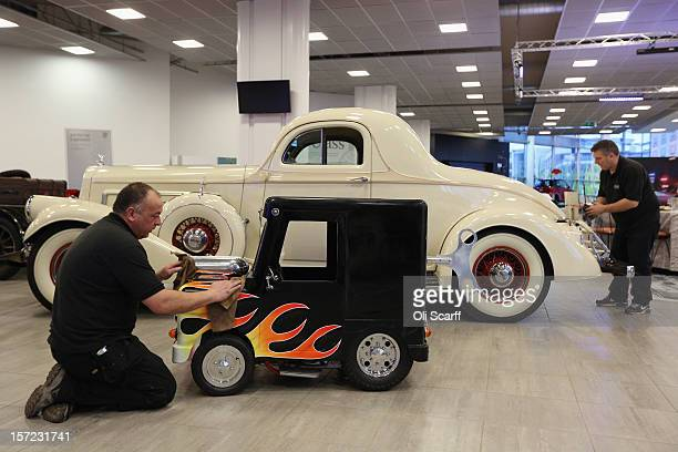 Workmen polish a Shanghai Shenke 'Wind Up' which is the world's smallest roadworthy car and a PierceArrow Model 845 which feature in Bonhams'...