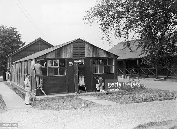 Workmen put the finishing touches to a reading room at the Olympic village in Richmond Park, Surrey, 28th May 1948. This 20-acre development,...