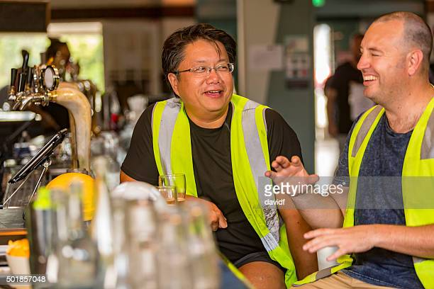 Workmen Relaxing With Beer After Work in High Visibility Clothes