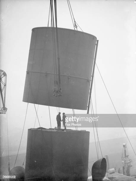 Workmen removing a funnel from the PO liner SS Ranpura at the Royal Albert Docks London during a refitting