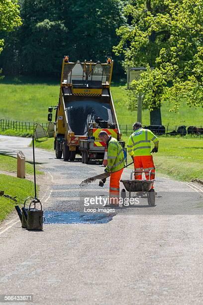 Workmen repairing damaged road surface.