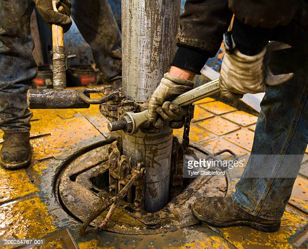 Workmen securing section of pipe on drilling platform, low section