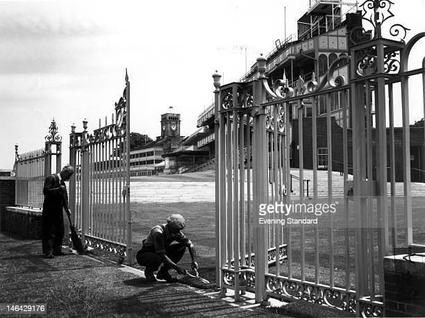 Workmen sprucing up the entrance to Ascot racecourse, 15th June 1959.