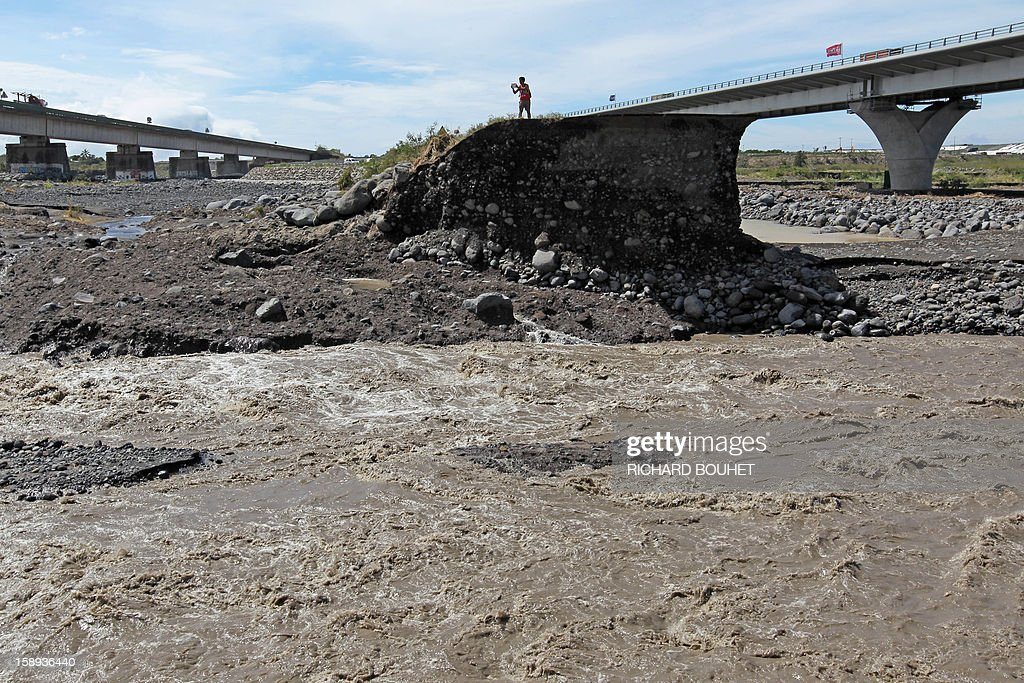 Workmen stand on a remaining piece of road crossing the river that links Saint Louis de la Reunion with Saint Pierre on January 4, 2013 near Saint Louis, on the French island of La Reunion, following the passing of cyclone Dumile. Winds of up to 180 kilometres per hour (110 miles per hour) and torrential rain caused extensive damage to the electricity network after cyclone Dumile passed within 90 kilometres of the island's west coast at around 0900 GMT.