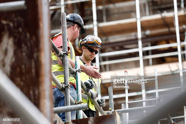 Workmen stand on scaffolding during building works at Balfour Beatty Plc's St James's Market construction site a joint Crown Estate and Oxford...