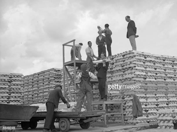 Workmen stockpiling aluminium ingots