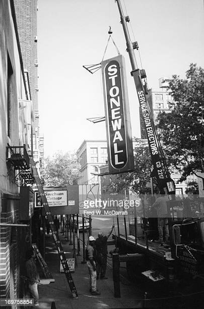 Workmen use a crane to remove the sign from the Stonewall bar New York New York October 11 1989 This marked the closing of the second iteration of...