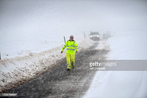 Workmen use diggers to clear drifting snow on the B797 on February 12 2020 on Wanlockhead Scotland A yellow warning for snow and ice remains in place...