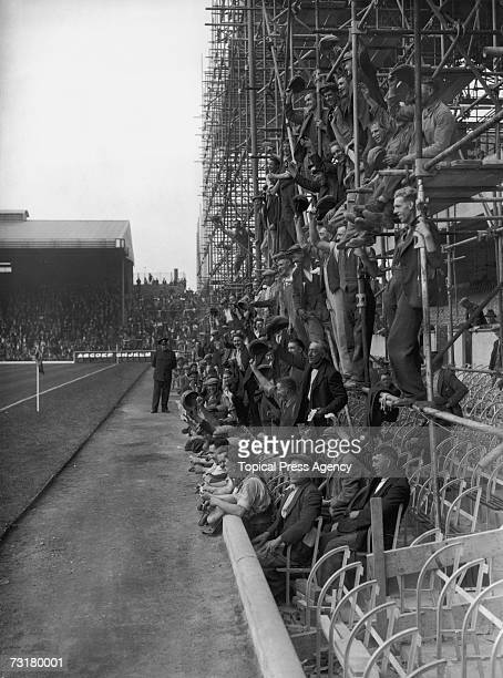 Workmen watching a trial match at Arsenal's Highbury stadium from the scaffolding of the nearly completed East Stand 15th August 1936