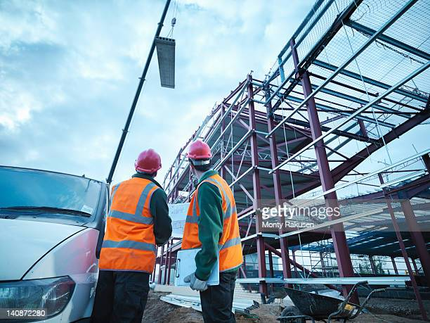 Workmen watching crane lifting roof panels onto steel construction frame on building site