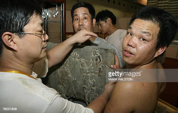 Workmen with an ancient Chinese stone sex carving as they prepare a display for the Chinese Sex Museum before the opening of the 3 day China...