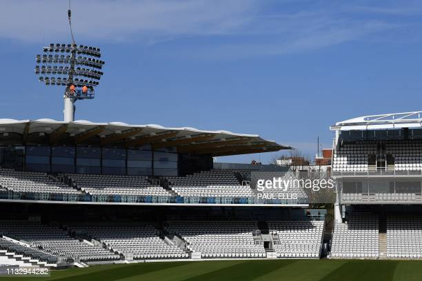 Workmen work on the floodlights at Lords cricket ground in London on March 26 following the announcement of their new head groundsman Karl McDermott....