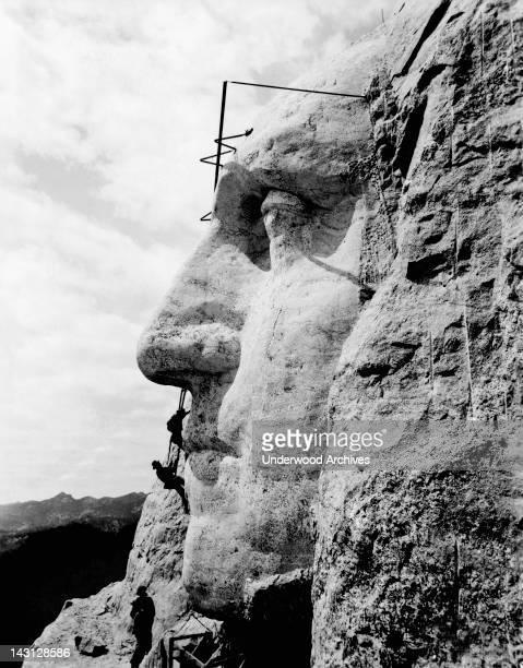 Workmen working on the face of George Washington Rushmore South Dakota circa 1932