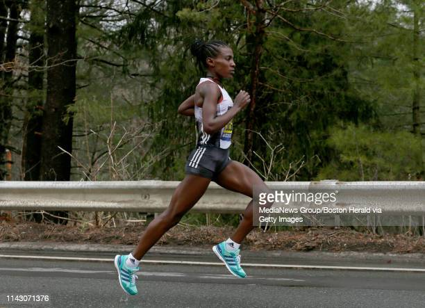 Worknesh Degefa of Ethiopia runs solo as she passes Wellesley College to go on to win the Boston Marathon on April 15 2019 in Wellesley Massachusetts