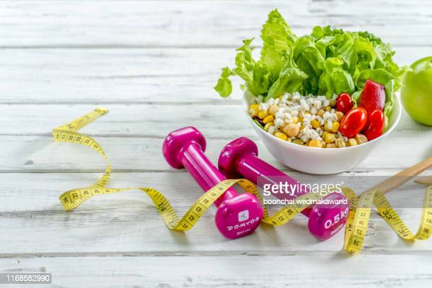 workout and fitness dieting copy space diary. healthy lifestyle concept. dumbbell, vegetable salad and measuring tape on rustic wooden table. - dumbbell stock pictures, royalty-free photos & images