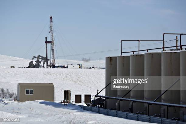 A workover rig stands beyond a storage tank battery at a crude oil collection facility in the Bakken Formation outside Williston North Dakota US on...