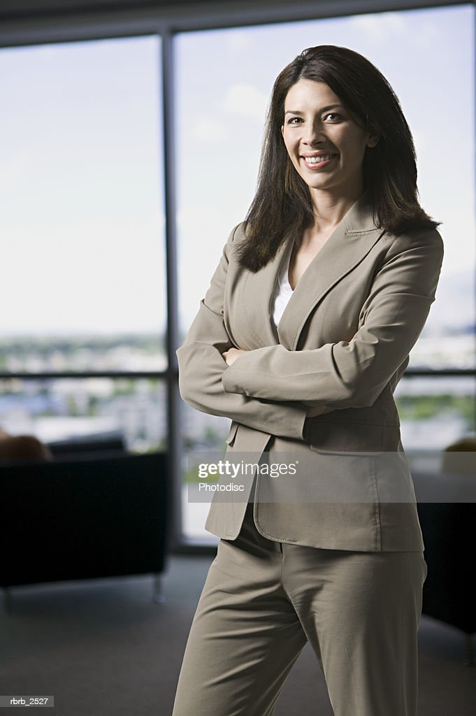 workplace shot of an adult business woman as she folds her arms and smiles : Foto de stock
