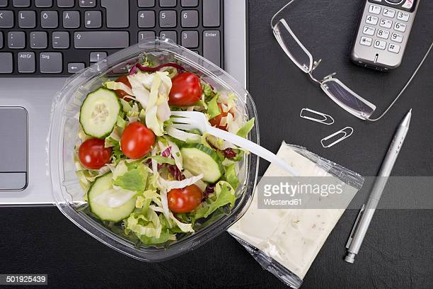 Workplace with mixed salad on laptop