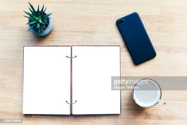 workplace with notepad, coffee and smartphone. - bovenkleding stockfoto's en -beelden