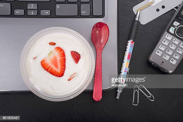 Workplace with strawberry yoghurt on laptop