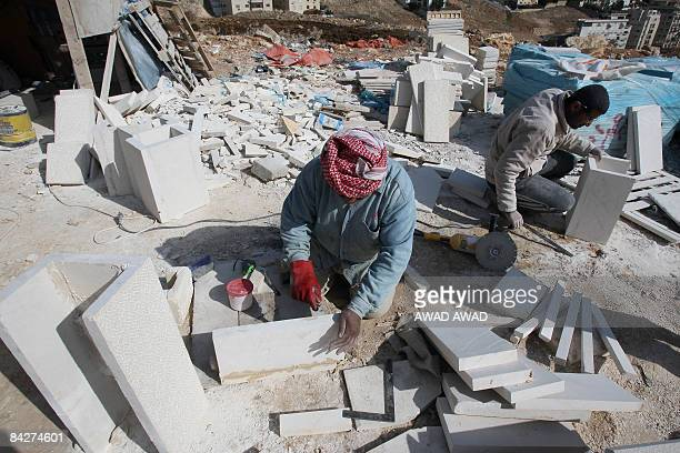 Works cut limestones at a site where an apartment building is being constructed in Amman on January 8 2009 Jordanians are snapping up houses despite...