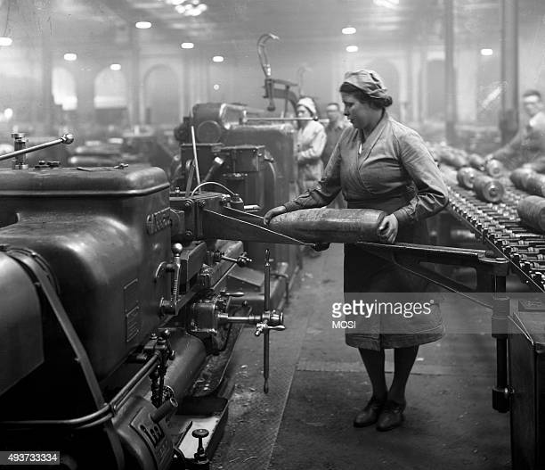 Works photograph of female employee transferring a 6 inch shell from the bench to a bore fuse hole machine Female employee transferring a 6 inch...