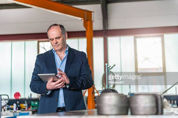 Workshop, senior man with digital tablet in front of gear drive