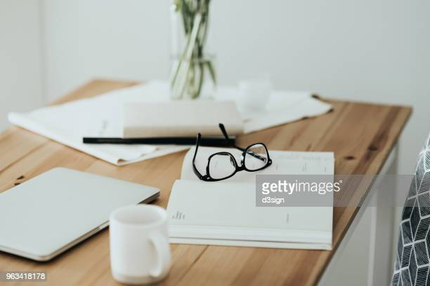 Workspace table with smartphone, eyeglasses, schedule calendar and coffee