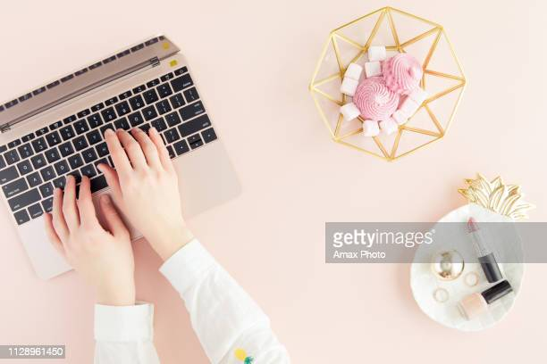 workspace with laptop, woman hands on pastel pink background. flat lay, top view office table desk. - flat lay stock pictures, royalty-free photos & images