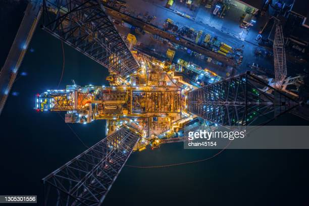 world at work drone view of oil and gas jack-up rig at the yard for maintenance with many vessels, the petroleum rig is applied for producing oil and gas in offshore in the petroleum industry. - south east asia stock pictures, royalty-free photos & images