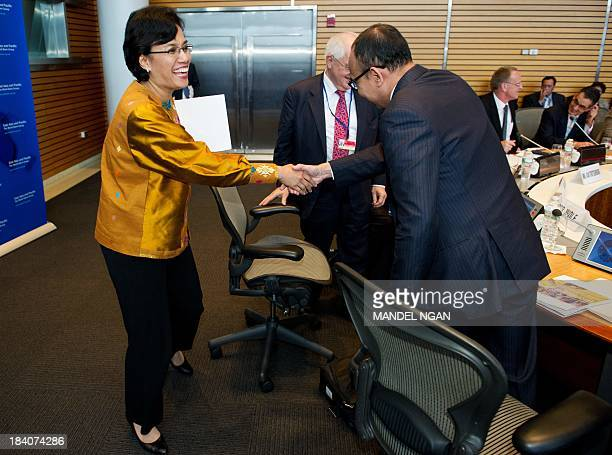 World Bank Chief Operating Officer and Managing Director Mulyani Indrawati shakes hands with Indonesian Finance Minister Muhammad Chatib Basri as she...
