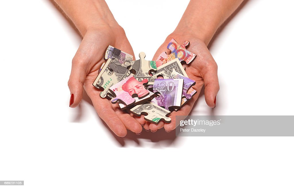 World bank note jigsaw pieces in hands : Stock Photo
