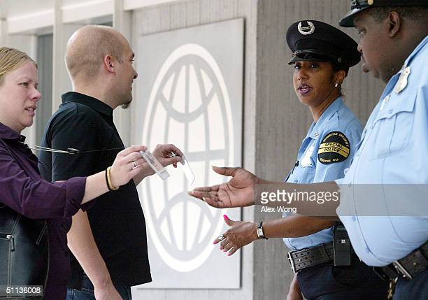 World Bank security guards check photo IDs before letting employees enter the World Bank headquarters August 2 2004 in Washington DC The Homeland...