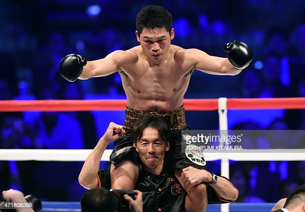 World Boxing Council super featherweight champion Takashi Miura of Japan is carried by his coach after beating challenger Billy Dib of Australia in...