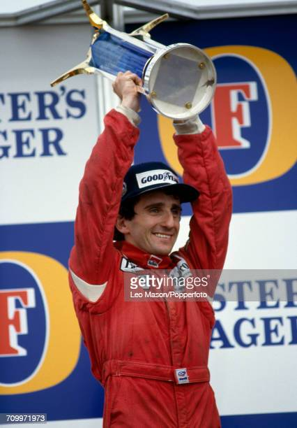 World Champion Alain Prost of France celebrates with the Formula One Cup after winning the Australian Grand Prix driving a McLaren MP4/2C with a TAG...