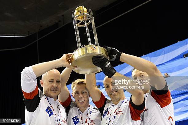 World Champion Canada's team skip Kevin Koe third Marc Kennedy second Brent Laing and lead Ben Hebert raise the trophy after winning the gold medal...
