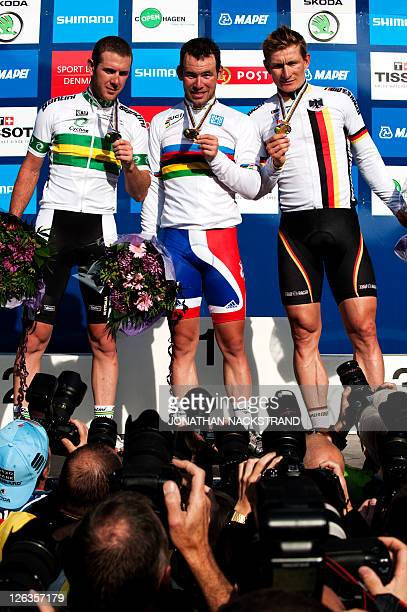 World Champion Mark Cavendish of Britain silver medalist Matthew Harley Goss of Australia and bronze medalist Andre Greipel of Germany pose to the...