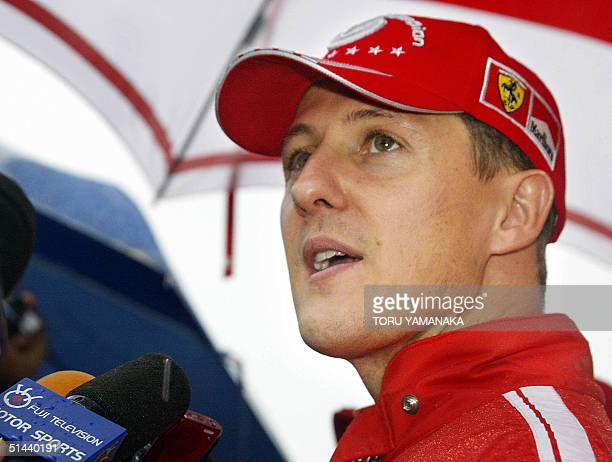 World champion Michael Schumacher of Germany is interviewed in front of his Ferrari team pit after the free practice session in Suzuka Circuit in...