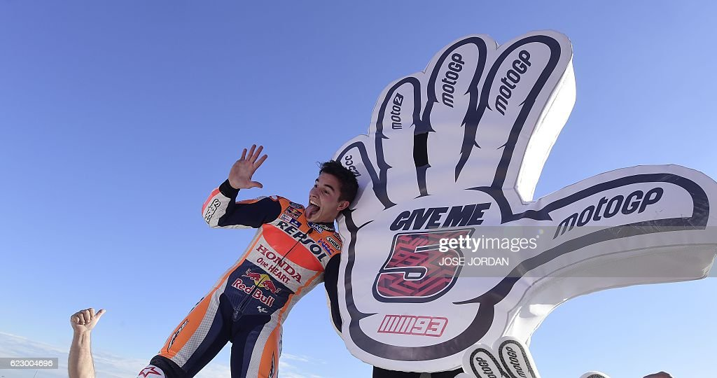 World Champion Repsol Honda Team's Spanish rider Marc Marquez celebrates after the MotoGP race of the Motul Comunidad Valenciana Grand Prix at the Ricardo Tormo racetrack in Cheste, on November 13, 2016. / AFP / JOSE