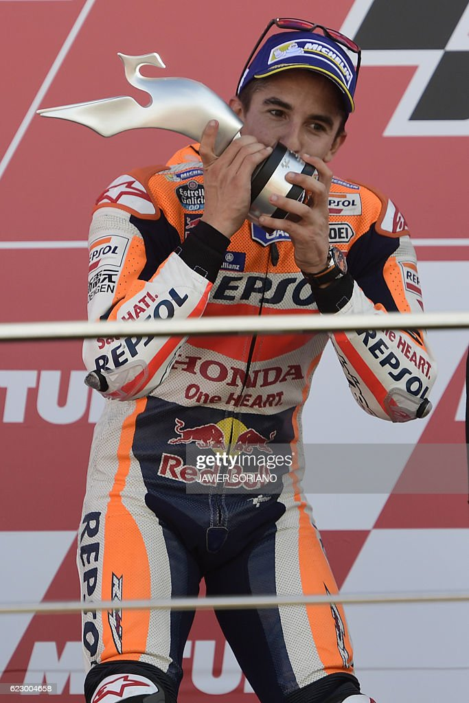 World Champion Repsol Honda Team's Spanish rider Marc Marquez celebrates on the podium after the MotoGP race of the Motul Comunidad Valenciana Grand Prix at the Ricardo Tormo racetrack in Cheste, on November 13, 2016. / AFP / JAVIER