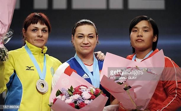 World champion Russia's Evstyukhina Nadezda silver medallist Kazaktan's Podobedova Svetlana and bronze medallist PRK Kim Un Ju pose on the podium...