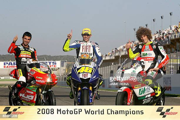 World champions France's Mike di Meglio Italian Moto GP champion Valentino Rossi and compatriot Marco Simoncelli pose on their bikes after the...