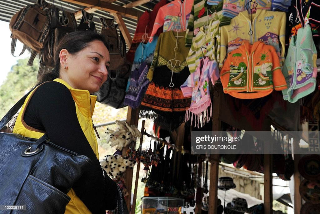 World chess champion Russian Alexandra Kosteniuk visits an indigenous stall upon her arrival to the train station near the Inca citadel of Machu-Picchu, 1,215 km south east of Lima, on May 23, 2010. Kosteniuk will play an exhibition set of games against Peruvian Under-16 female world champion Deysi Cori.